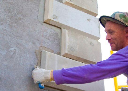 На фото мастер крепит декор на угол здания