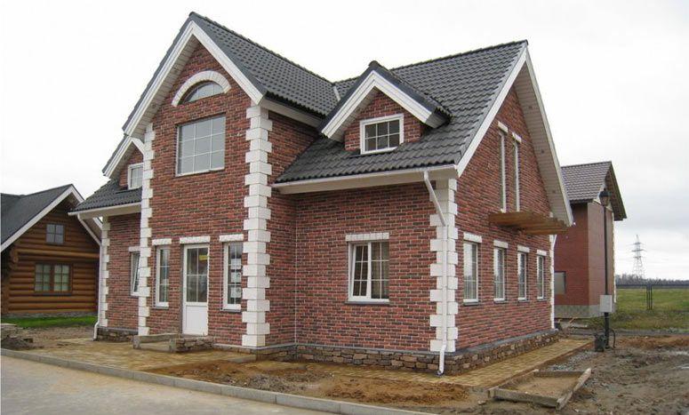 Фасад дома покрыт темным искусственным камнем