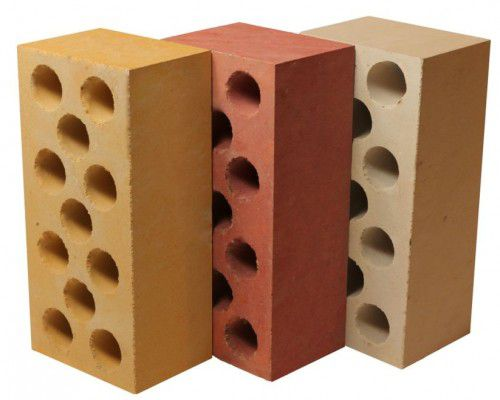 Несколько силикатных кирпичей, с круглыми полостями, в разных цветовых решениях.