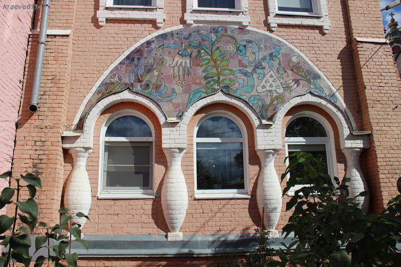 Тройное окно первого этажа увенчано полуциркульным розово-лиловым панно