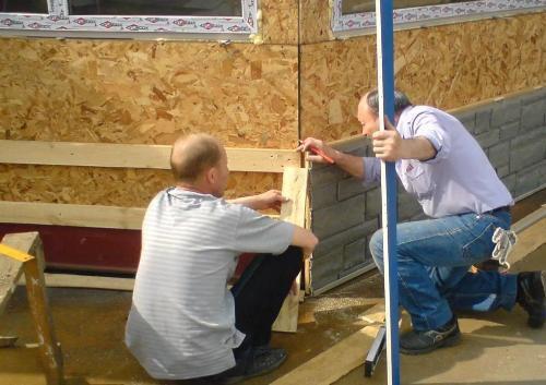 Двое монтажников устанавливают панели на цокольный этаж дома.