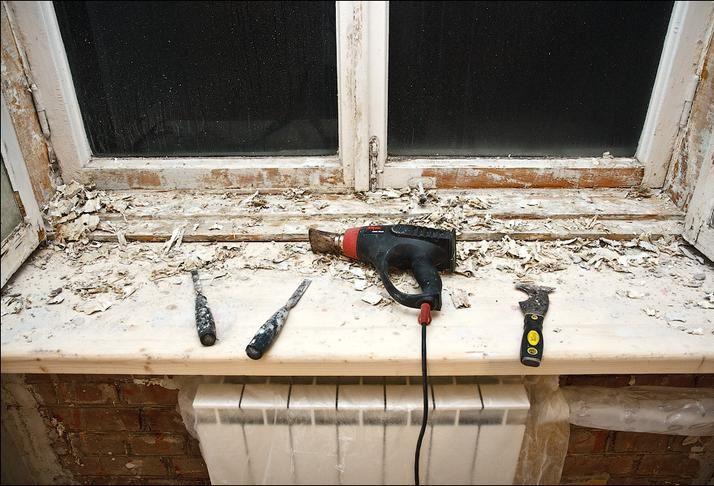 С помощью строительного фена и шпателя начинаем снимать старую краску