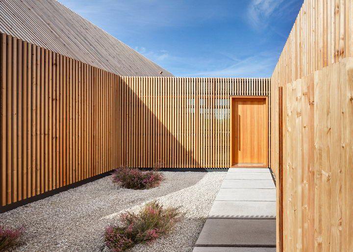 И стены и окна в лицевой части дома облицованы деревянными экранами, чтобы обеспечить конфиденциальность для жителей