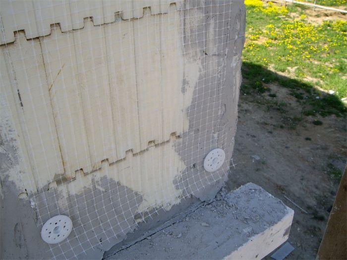 На фото – установка армировочной сетки на фасаде дома