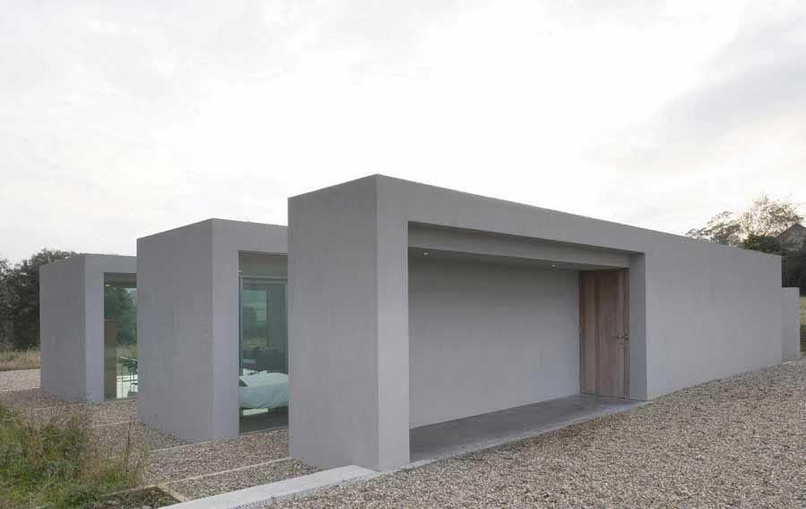 На фото фасад дома в стиле минимализм, пример отделки декоративной штукатуркой с имитацией бетона
