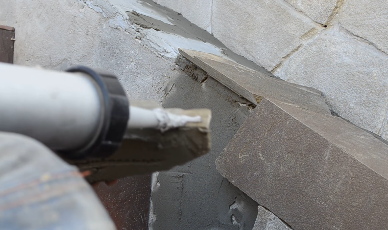 Чтобы лучше соединить два камня на внешнем углу, наносим немного полиуретанового клея на торец камня