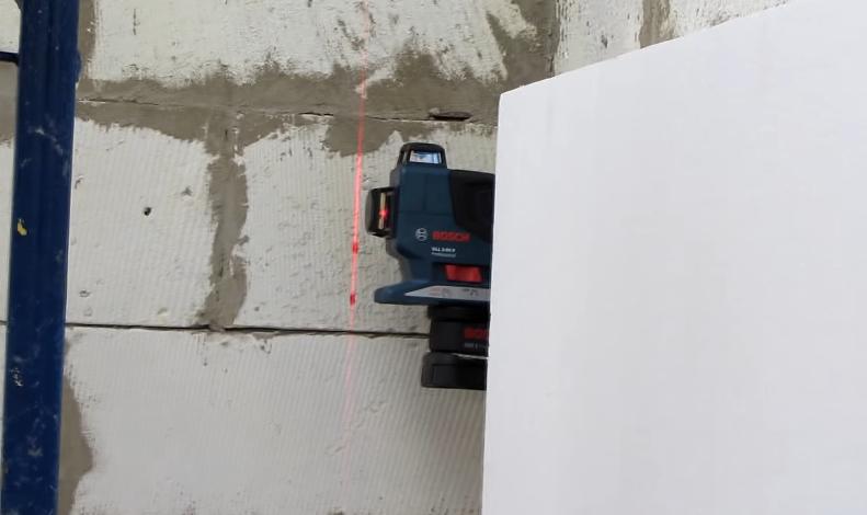 Использование лазерного нивелира для контроля уровня приклеивания листов пенопласта