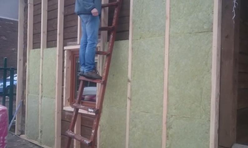 Укладка плит минваты. На фото можно заметить ошибку строителей - отсутствие изоляционной мембраны между ватой и деревянной стеной