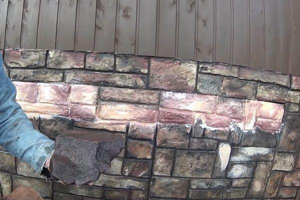 В центре можно заметить участок цоколя, который еще не был обработан темной краской. Также можно увидеть, что в качестве базового было выбрано несколько оттенков – это придает отделке большее соответствие натуральному камню, неоднородному по своему внешнему виду