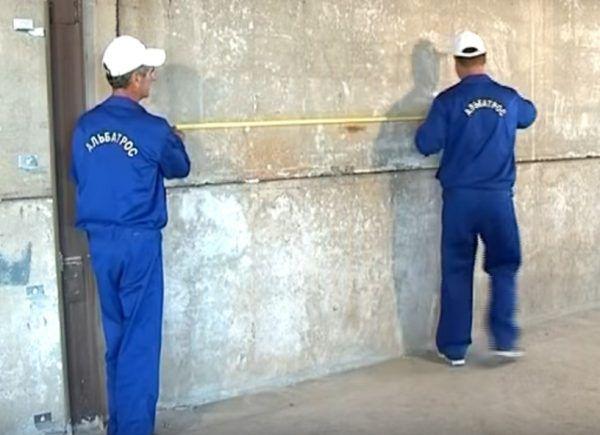 Производятся замеры на стене