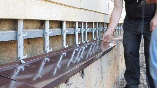 Строитель устанавливает отливы на цоколь и проводит замеры.