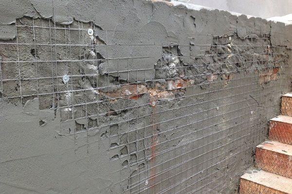 Процесс штукатурки стены по закрепленной металлической сетке