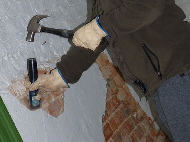 Скалывание старой штукатурки с кирпичной стены