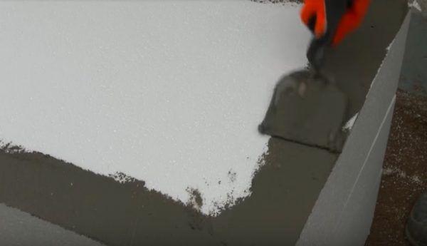 Нанесение первого тонкого слоя клея по периметру блока